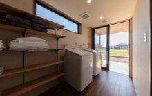 洗濯室内観 2つの洗濯機に壁面を利用した収納棚 洗面室屋外に物干しコーナー
