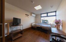 利用者短期ステイ用の個室1内観 介護ベッドにテレビ 小さなテーブルが置かれる