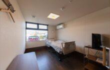 利用者短期ステイ用の個室3内観 介護ベッドにテレビ 小さなテーブルが置かれる