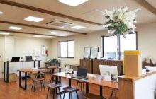 2階スタッフルーム 中央にオフィス用ワークテーブルと腰掛け椅子 壁面に収納キャビネット設置