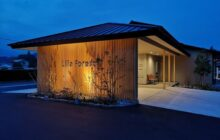 夕景の建物外観 エントランス格子壁に照明が当たる